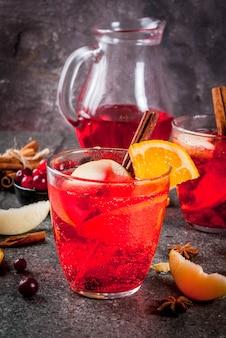 Bebidas frias de outono e inverno, soco de natal férias laranja e amora com canela, estrelas de anis, no espaço da cópia de fundo preto