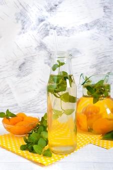 Bebidas frias de verão. deliciosa bebida refrescante com damasco e hortelã em copos em um fundo branco de madeira. compota de frutas.