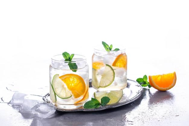Bebidas geladas com gelo e hortelã. coquetel de laranja em fundo cinza de concreto