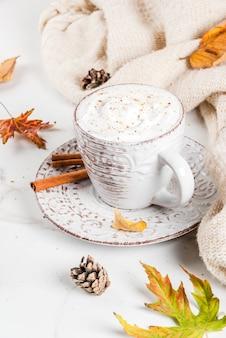 Bebidas quentes de outono latte de abóbora com chantilly, canela e anis em uma mesa de mármore branca com uma blusa (cobertor), folhas de outono e cones de abeto