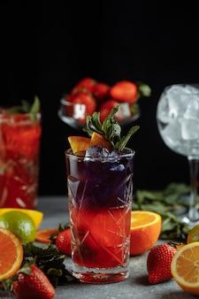 Bebidas refrescantes coloridas para o verão, suco de limonada de morango com cubos de gelo nos copos decorados com limões frescos fatiados.