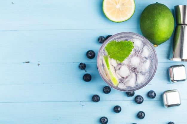Bebidas refrescantes de verão, limonada de mirtilo ou coquetel de mojito com limão, mirtilos frescos e hortelã,