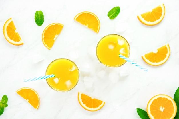 Bebidas refrescantes para o verão, suco de laranja com cubos de gelo nos copos