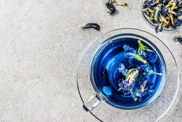 Bebidas saudáveis, chá de flor de ervilha de borboleta azul orgânica com limas e limões, espaço de cópia de plano de fundo cinza concreto