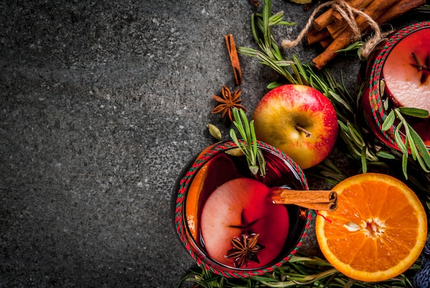 Bebidas tradicionais de inverno e outono. cocktails de natal e ação de graças. vinho quente com laranja, maçã, alecrim, canela e especiarias em uma pedra escura, vista superior