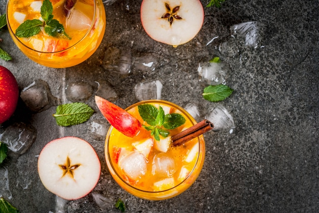 Bebidas tradicionais de outono, coquetéis de mojito de cidra de maçã com menta, canela e gelo. na mesa de pedra preta, copie a vista superior do espaço