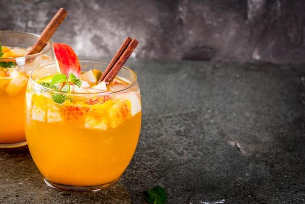Bebidas tradicionais de outono, coquetéis de mojito de cidra de maçã com menta, canela e gelo. na mesa de pedra preta, copie o espaço