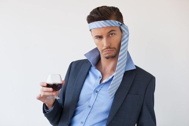 Bebido homem de negócio com laço na cabeça e vidro