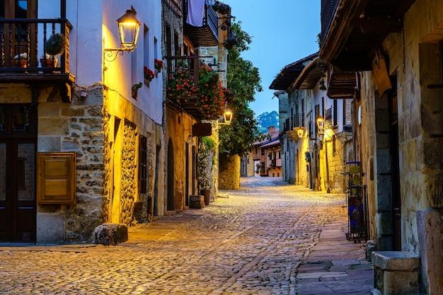 Beco estreito da velha cidade de pedra, com ruas de paralelepípedos iluminadas à noite.