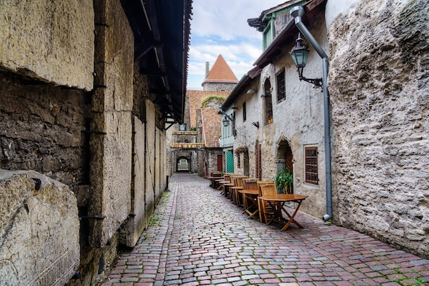 Beco medieval com casas de pedra e a torre do castelo em tallinn, estônia.