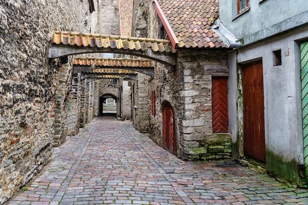 Beco medieval encantador com arcos de azulejos em tallinn, estônia.