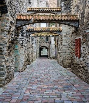Beco medieval estreito com arcos de azulejos na cidade estoniana de tallinn.