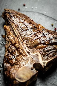 Beef t-bone suculento bife bife mal passado com especiarias. cozinha americana. o conceito de cozinhar carne. t-bone steak grelhado raro médio, churrasco porterhouse wagyu envelhecido.