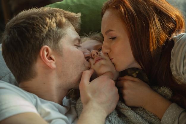 Beijando com todo amor. família passando bons momentos juntos em casa, parece feliz e alegre. mãe, pai e filha se divertindo, deitados no sofá. união, conforto do lar, amor, conceito de relações.