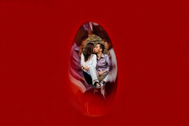 Beijando o casal apaixonado. jovem casal apaixonado sentado no chão e beijando. história de amor