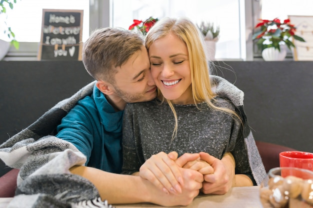 Beijando o jovem casal sentado no café juntos sob o cobertor