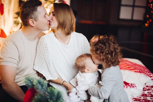 Beijando os pais com crianças abraços no natal.