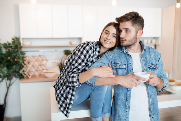 Beijando um jovem feliz e uma mulher na cozinha, café da manhã, casal juntos pela manhã, sorrindo, tomando chá
