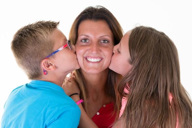 Beijo alegre da mãe pelo filho filha menino e menina crianças conceito família feliz amor