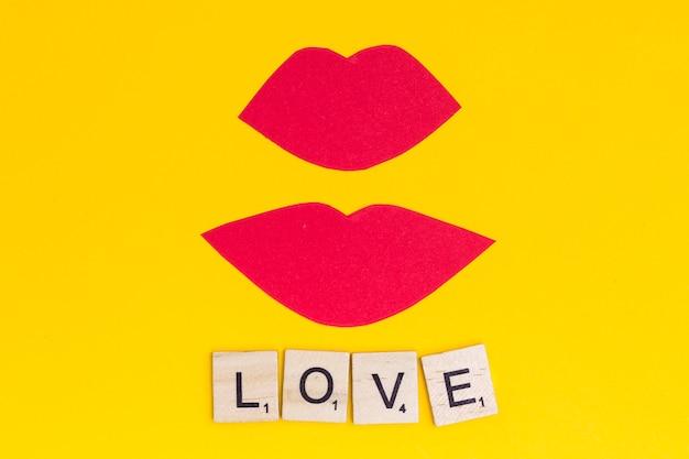 Beijo de lábios cor de rosa com amor de frase no fundo brilhante