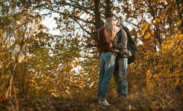 Beijo de mochileiros no amor abraçando em pé sozinho no contexto da floresta de outono ao ar livre