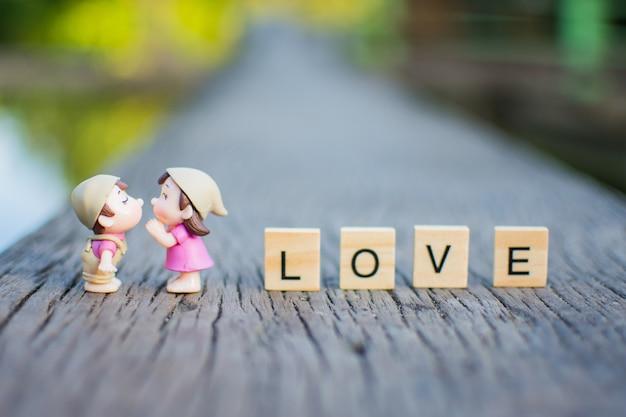 Beijo diminuto do amor dos pares na tabela de madeira e no amor de madeira do texto.