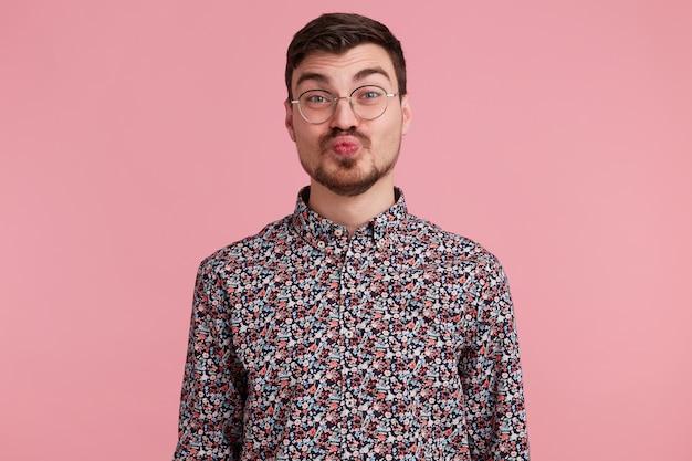 Beijo doce diretamente para a câmera. retrato de um cara simpático de óculos mandando beijo no ar com beicinho, isolado no fundo rosa, mostra ternura