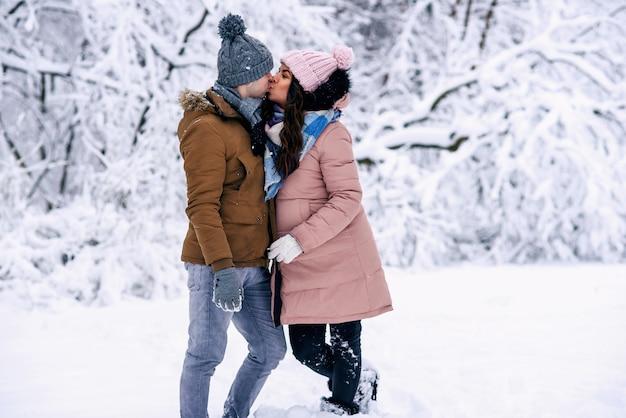 Beijo gentil de uma linda mulher grávida com o marido em um parque de inverno nevado ao fundo