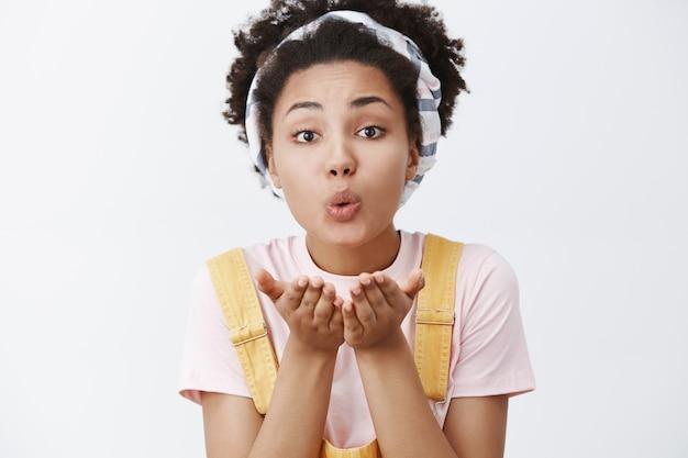 Beijos calorosos para você, querida. retrato de uma mulher afro-americana fofa e terna, feminina, com uma faixa na cabeça e um macacão amarelo, segurando as palmas das mãos sobre a boca, soprando um mwah com os lábios dobrados e um olhar carinhoso