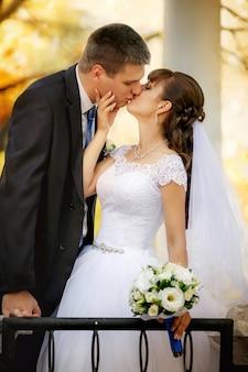 Beijos do noivo e da noiva no parque