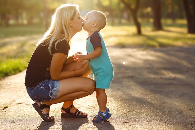 Beijos e abraços de mãe e filho. mãe e filho a passear no parque de verão.