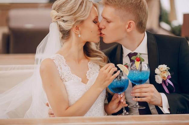 Beijos newlyweds e beber um cocktail