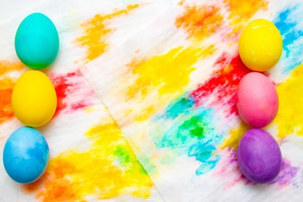 Beira colorida do ovo do ovo da páscoa contra no fundo multicolorido. quadro, copyspace.