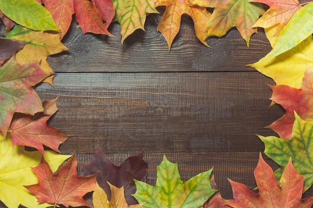 Beira das folhas coloridas do outono na placa de madeira. conceito de queda.