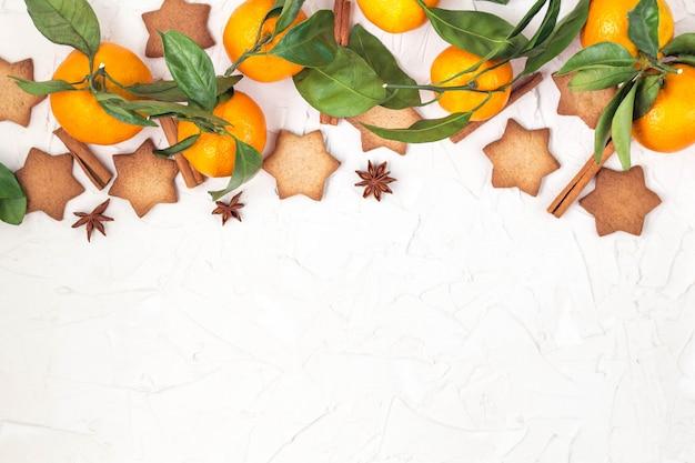 Beira de biscoitos da estrela do natal com especiarias e mandarino no fundo branco com copyspace.