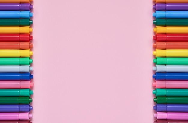 Beira de penas de ponta de feltro coloridas no fundo cor-de-rosa com copyspace. vista do topo