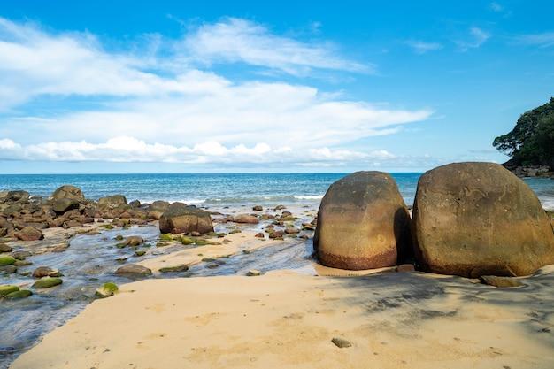 Beira-mar com pedras contra o céu azul de nuvem minúscula. Foto Premium