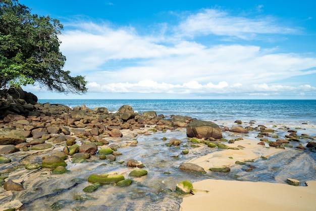 Beira-mar com pedras contra o céu azul de nuvem minúscula.