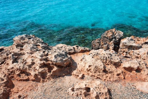 Beira-mar com pedras e água do mar transparente e clara. fundo marinho natural. papel de parede azul oceano, onda do mar em dia de sol. águas cristalinas e falésias alaranjadas do mar tropical