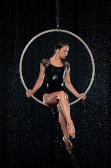 Bela acrobata feminina magro sentado no aro aéreo sob chuva em fundo preto.