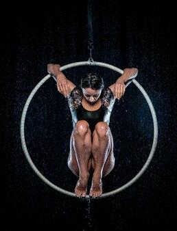 Bela acrobata feminina sentada em pose simétrica em aro aéreo sob chuva em fundo preto.