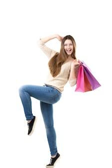Bela adolescente alegremente dançando com bolsas de compras rosa em suas mãos