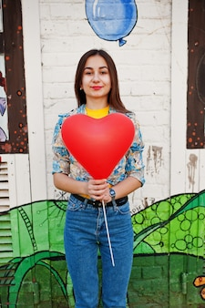 Bela adolescente andando com balão de coração, usar jeans perto de parede grafite.