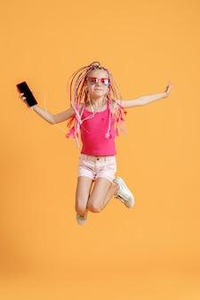 Bela adolescente com dreadlocks pulando com o celular na mão e ouvir música em fones de ouvido