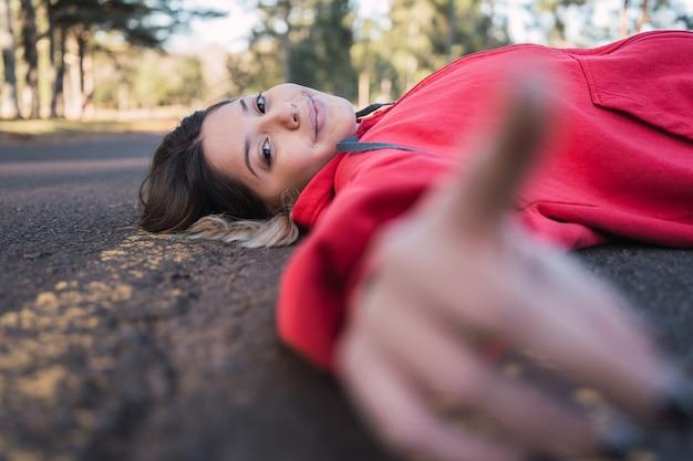 Bela adolescente deitada na estrada de asfalto.