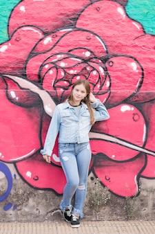 Bela adolescente em pé perto da parede do graffiti