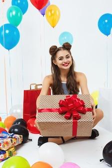 Bela adolescente em roupas extravagantes, mostrando enorme caixa de presente