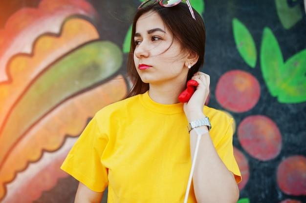 Bela adolescente em t-shirt amarela perto da parede do graffiti.