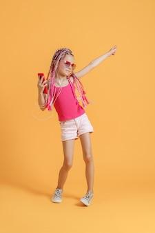 Bela adolescente europeia com dreadlocks com celular na mão