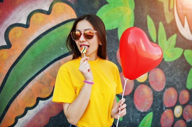 Bela adolescente lambendo pirulito com óculos, balão de coração na mão, t-shirt amarela perto da parede de graffiti.